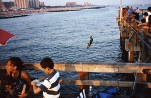 A diver jumps off the pier at Coney Island